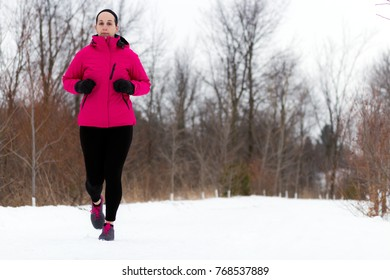 Winter snow runner woman running outside on cold winter day. Fit healthy lifestyle concept with beautiful young fitness model. Caucasian female model jogging outside in full length.