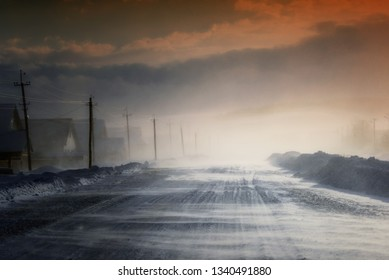 Winter snow storm and blizzard on a rural village street with houses and natural sunlight with nobody outdoors
