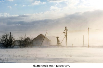 Winter snow storm and blizzard on a rural village street with houses and natural sunlight