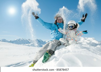 Winter, snow, sun and fun - happy skiers playing in snow