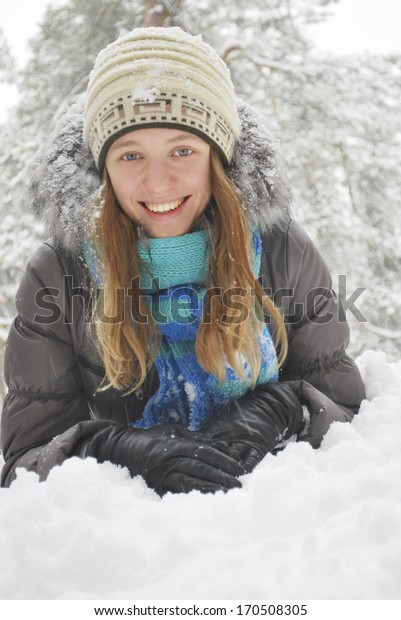 Winter, snow-covered forest, lies the beautiful long-haired girl in the snow.