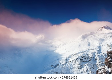 Winter snow-covered mountains at sunset. Creative toning effect. Beautiful winter landscape