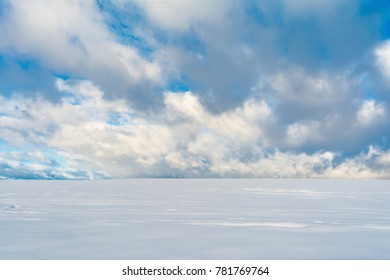 winter snowfield and cloudy sky with large clouds, winter landscape