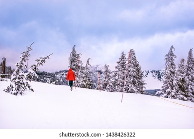 Winter snowshoe hiking in mountains. Active outdoorsman hikes to the top of a mountain range at sunset. Crater Lake National Park. Portland. Oregon. United States.