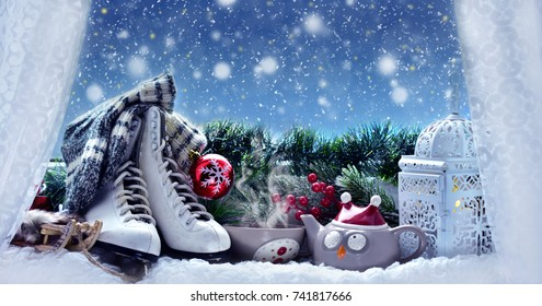 winter snowy evening with cup of hot tea,old figure skates and vintage style lantern and Christmas decoration on window sill