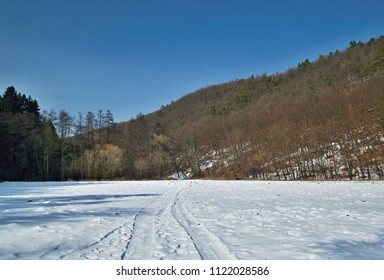 Winter snowy landscape with wooded hill under blue sky