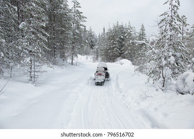 Winter snowy lanscape with road end athletes on a snowmobile