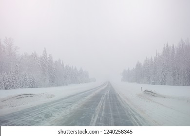 Winter snowy road in a forest without cars. Dangerous driving conditions in winter in cloudy weather.