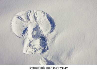 Winter, snowy surface, natural texture. An angel print with open wings. Christmas, waiting for a miracle. Top view, copy space.