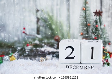 Winter Solstice. White wood calendar blocks with the date December 21st and Christmas decorations with snow. Selective focus with blurred background.