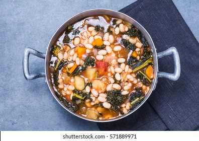 Winter soup with beans, kale, vegetables top view.Typical tuscan soup ribollita.