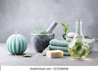 Winter spa and bath concept. Oil for body massage, sea stones, vanilla soap with coconut for scrub, towels, eucalyptus leaves in a mortar and branch fresh bamboo on light grey background. Copy space