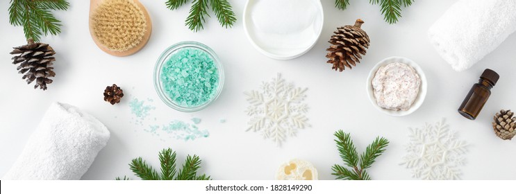 Winter Spa Concept and Skin Care products, fir branches and snowflakes on white background, flat lay, copy space.  Seasonal beauty routine and skin care concept.
