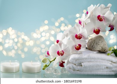 Winter spa decorations with orchid, 2 candles and towel on blue background and defocused garland lights.