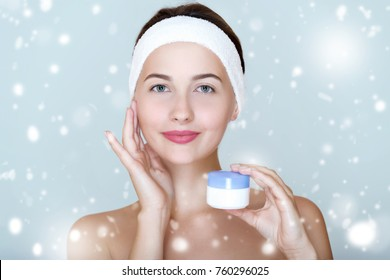 Winter spa face care.  Woman  with clean perfect skin  holding of emollient cream.