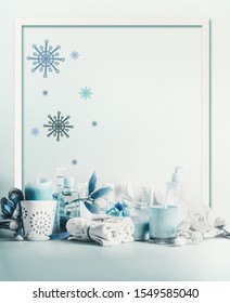 Winter spa and wellness concept. Winter skin and body care. Cosmetic products. Holiday spa day. Frame. Blue composition of candles, towels, and flowers. Winter beauty