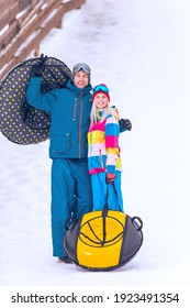 Winter Sport and Activities. Portrait of Lovely Caucasian Couple Having Tube Activities In Winter Time On Skiing Resort In Mountains. Vertical Image