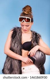 Winter sport activity concept. Atractive smiling woman wearing black bra, ski goggles and furry waistcoat holding helmet, blue background studio shot.