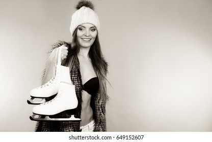 Winter sport activity concept. Atractive smiling girl wearing black bra, warm hat and furry waistcoat holding ice skates, black and white studio shot.