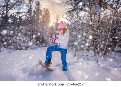 Winter sport activity. Woman with snowshoes on fluffy snow in forest. Beautiful landscape with coniferous trees and white snow. Post processing snowflakes effect