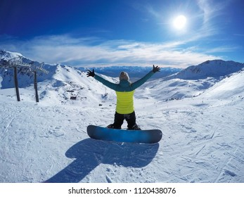 Winter sport activity.Happy woman with snowboard holding hands up open, freedom, enjoying a winter, cold season. Having fun on the snow, mountains, ski area, Remarkables, New Zealand, Queenstown