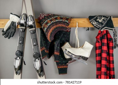 Winter sport background with old school sweater, knitted woolen hat, ice skates, gloves and skies over gray. Winter healthy leisure lifestyle concept