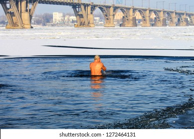 Winter sport. An elderly man swims in a winter river covered with ice during the Orthodox holiday Epiphany. Hardening. Dnipro city, Dnepropetrovsk, Ukraine