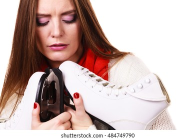 Winter sport equipment concept. Close up picture of ice skates. Woman with white jumper.