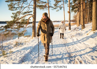 Winter sport in Finland - nordic walking. Man and Senior woman hiking in cold forest. Active people outdoors. Scenic peaceful Finnish landscape with snow.