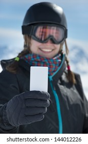 Winter sport girl with blank lift pass card smiling at camera. Concept to illustrate ski admission fee