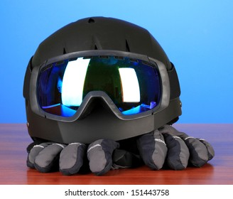 Winter sport glasses, helmet and gloves, on blue background