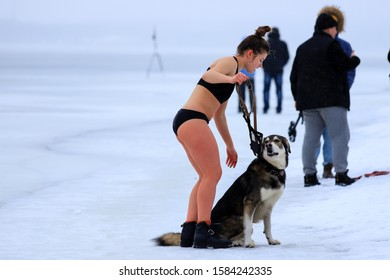 Winter sport, hardening in winter. A girl in a bathing suit with a dog stands near a river covered with ice and snow.  Orthodox holidayof Epiphany, Dnipro city, Dnepropetrovsk, Ukraine, 19 01 2019