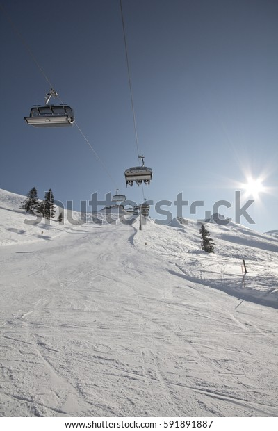 Winter Sport Resort Montafon. Wonderful weather for winter sport action in Austria. Great view over some mountain ranges and peaks in a awesome snow landscape. Snowboarder. Skier.