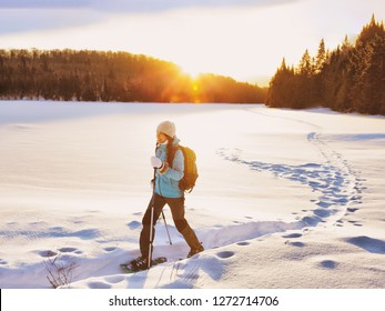 Winter sport woman hiking in snowshoes. Snowshoeing girl in the snow with shoe equipment for outdoor walking in forest trail. Quebec, Canada.
