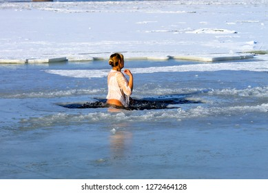 Winter sport. A woman swims in the winter river covered with ice during the Orthodox holiday of Epiphany. Hardening. Dnipro city, Dnepropetrovsk, Ukraine