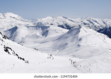 winter sports and activities such as skiing, snowboarding, sledding, and ice skating, resort with many ski tracks and snowy tops, snowboarder is jumping with snowboard from snow hill