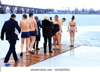 Winter sports, hardening. Group of people stand and swim in the winter in the ice hole on the Dnieper River during the Orthodox holiday Epiphany. Dnipro city, Dnepropetrovsk, Ukraine,19.01 2019.