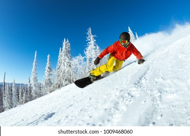 Winter sports photo with very fast snowboarder slides at ski slope
