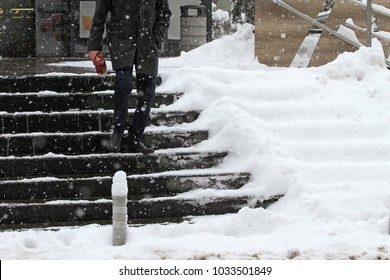Winter. Stairs. People walk on a very snowy stairs. Uncleaned icy stairs in front the buildings, slippery stairs