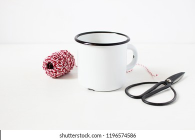 Winter still life composition with blank white metal coffee mug, vitage scissors and red decorative gift rope on white table background. Christmas styled stock photo, rustic scene. Product mockup.