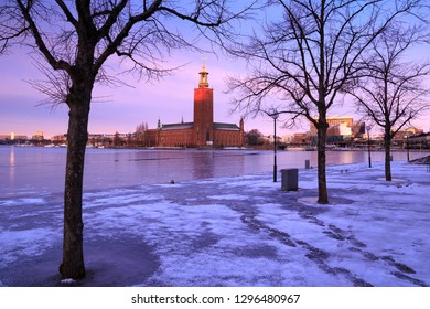 Winter in Stockholm, Sweden. City Hall (Stockholms stadshus, Stadshuset) seen from Riddarholmen, through bare branches of trees, hit by the first rays of sun at sunrise. Frozen lake, ice and snow.