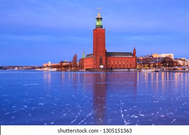 Winter in Stockholm, Sweden. Red brick tower of City Hall (Stockholms stadshus, Stadshuset) at dawn, before sunrise. Ice on frozen lake Malaren in the foreground.