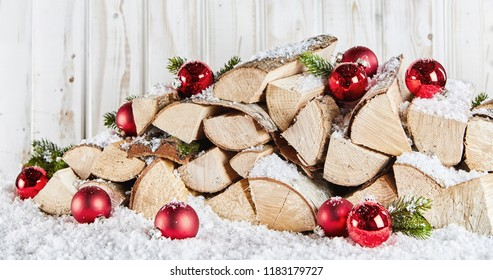 Winter stockpile of wood logs in snow at Xmas decorated with colorful red baubles and pine foliage against a white wooden rustic wall