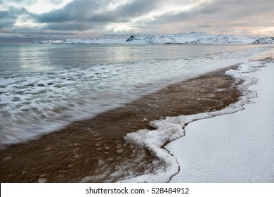Winter storm at the Arctic Ocean at sunrise. Barents Sea, the settlement of Teriberka, Russia.