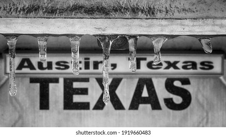"""Winter storm in Texas. Sign """"Austin, Texas"""" behind icicles. Selective focus on icicles, black and white image."""