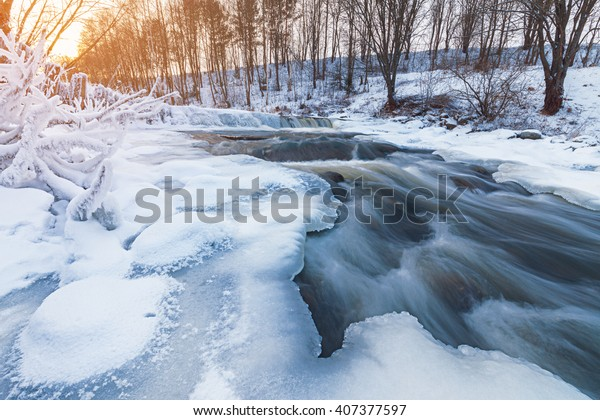 Winter stream encased in ice with a dusting of snow and hoarfrost. Long exposure, with blurred water.