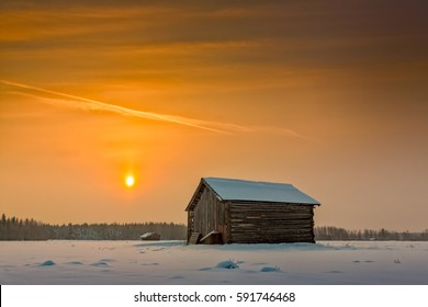 The winter sun rises on a cold morning in the Northern Finland. The barns are standing lonely on the snowy fields waiting for the spring.