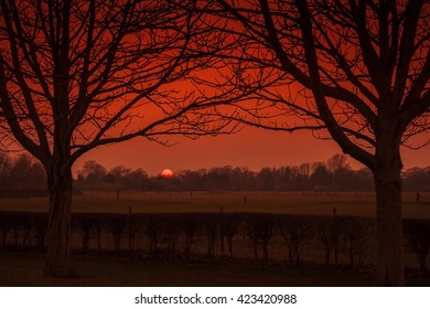 Winter sun setting over Dorney Reach between two trees.