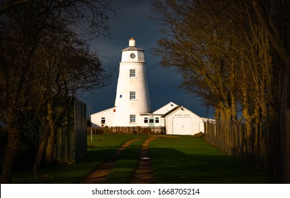 Winter sunlight falls on East Bank Lighthouse famous for The Snow Goose, against a stormy sky in Sutton Bridge, River Nene, Spalding, Lincolnshire