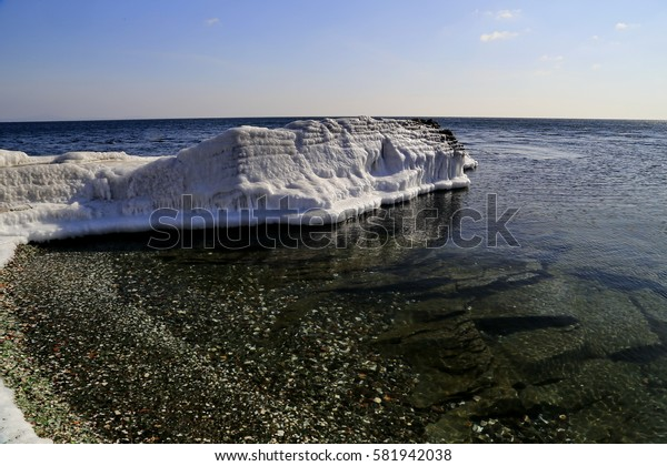 winter. sunny day. seascape. coastal stones are covered with ice. calm and clear water. reflection. stones under water.  blue sky with clouds. empty horizon.